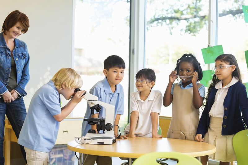 Ford motor company STEAM Education | Students look at microscope | Tropical Ford in Orlando, FL